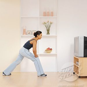 Side view of a woman exercising at home while watching TV