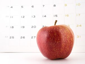 Close-up of an apple with a calendar on the background. Intended to illustrate a proverb 'An apple a day keeps the doctor away'